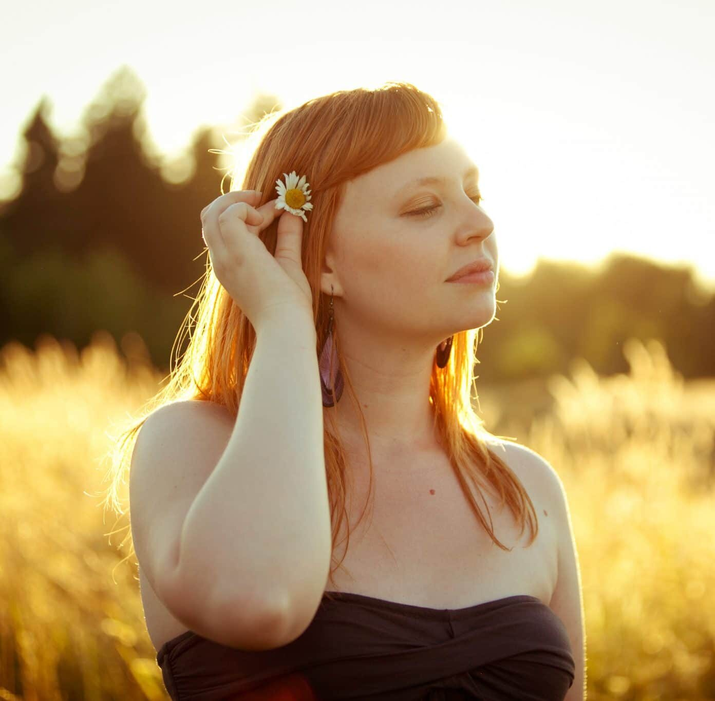 a girl putting a flower behind her ear in a meadow.