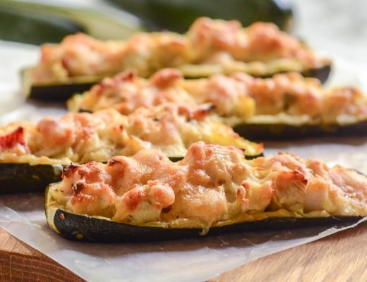 Close up image of four crab and artichoke stuffed zucchini on wax paper and wooden cutting board