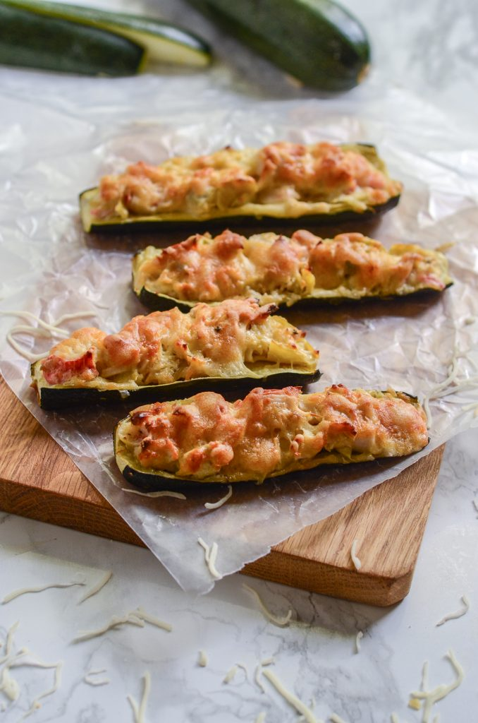 Overhead image of four crab and artichoke stuffed zucchini on wax paper and wooden cutting board