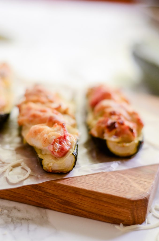 Close up of crab and artichoke stuffed zucchini on wax paper and wooden cutting board