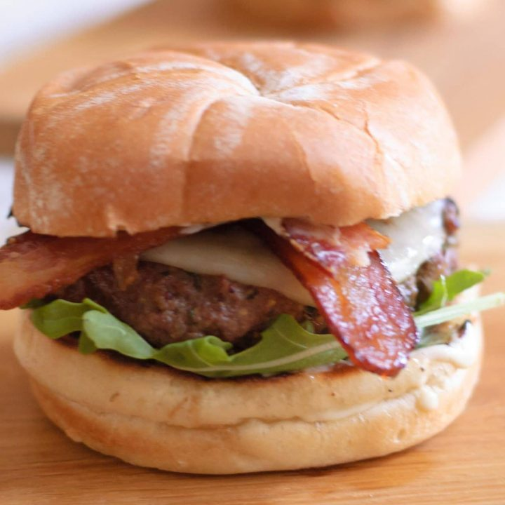 A caramelized onion burger with bacon sticking out of it.