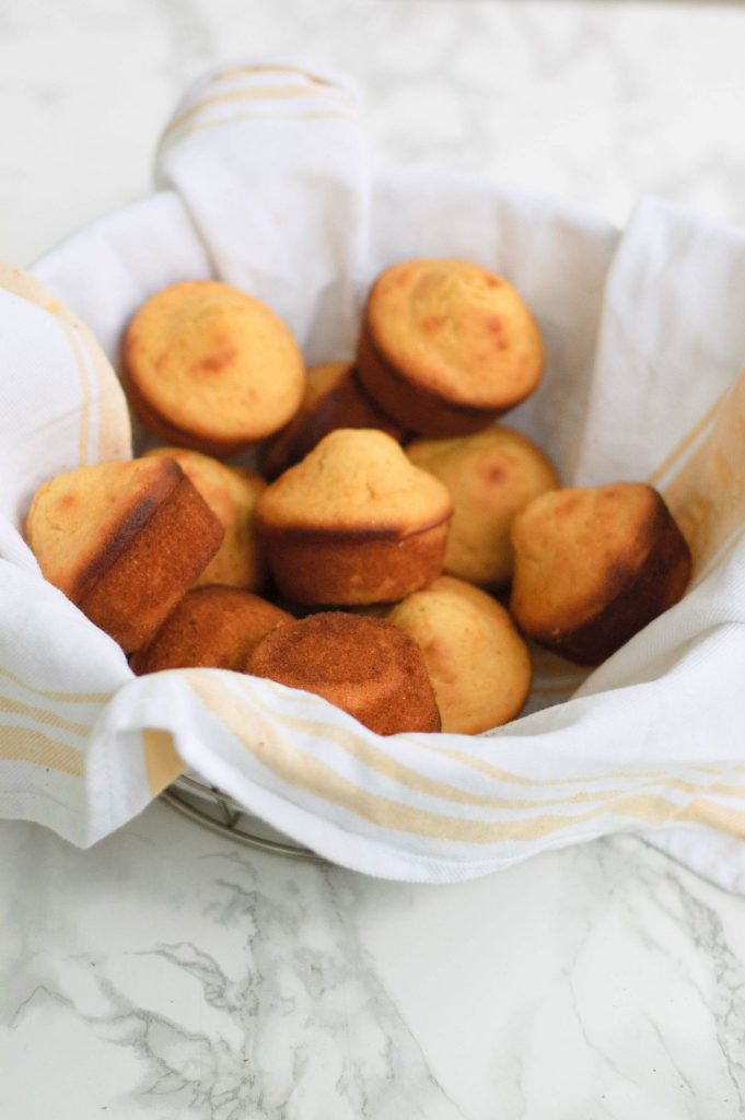 A towel lined basket of corn muffins.