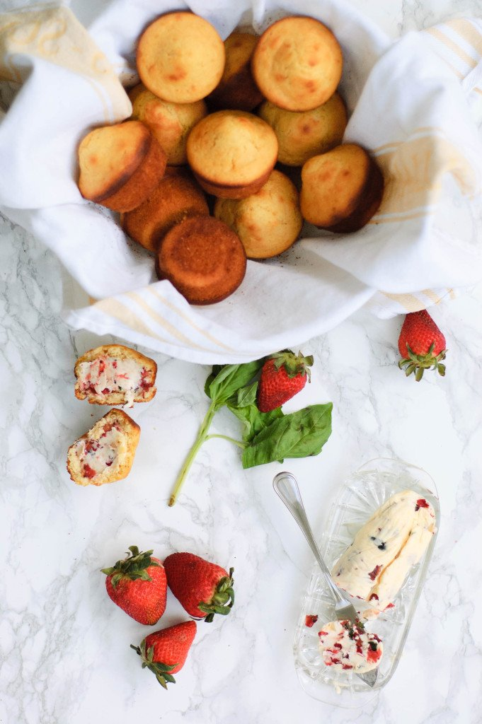 A basket of honey corn muffins next to butter, basil and strawberries.