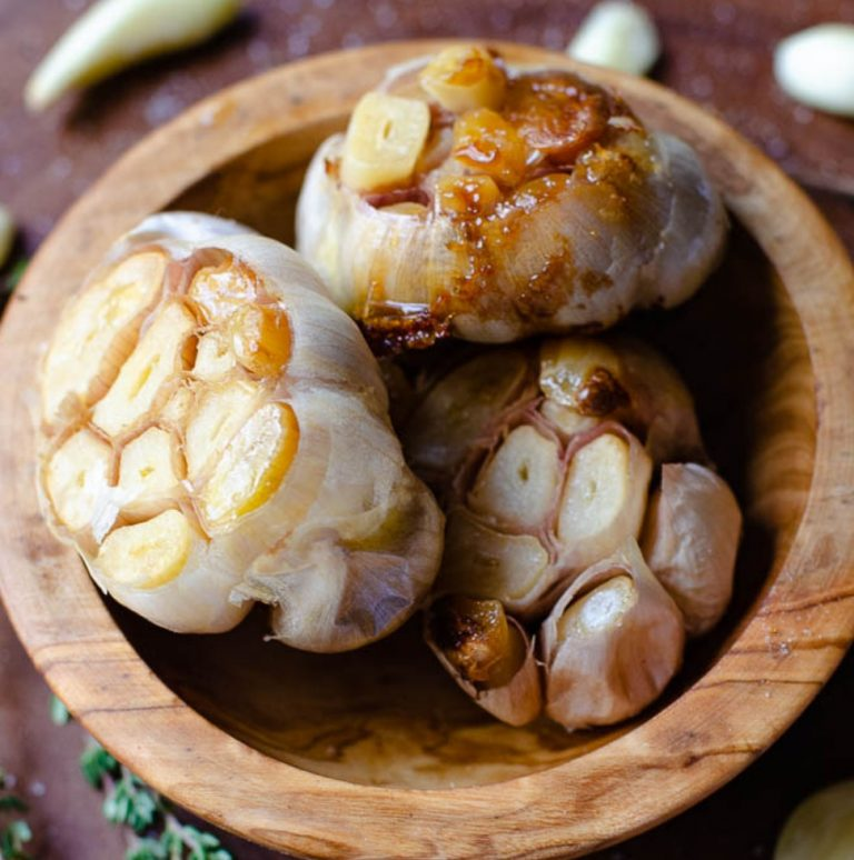 Close up of three heads of roasted garlic inside a wooden bowl.
