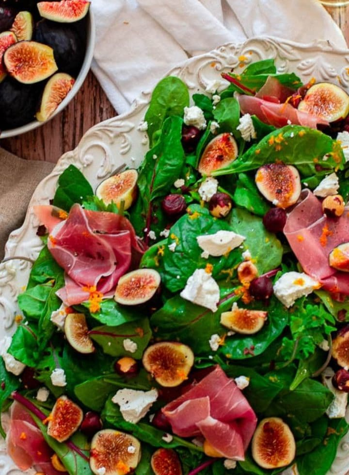 fig salad with goat cheese on a white platter.