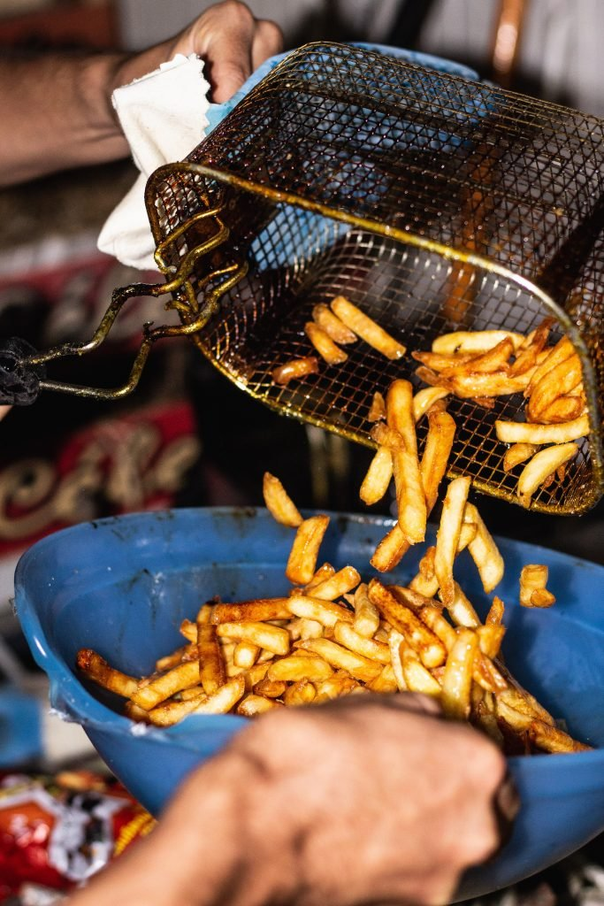 french fries being poured from a fryer basket into a blue bowl.
