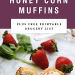 a close up of a cut honey corn muffin next to strawberries