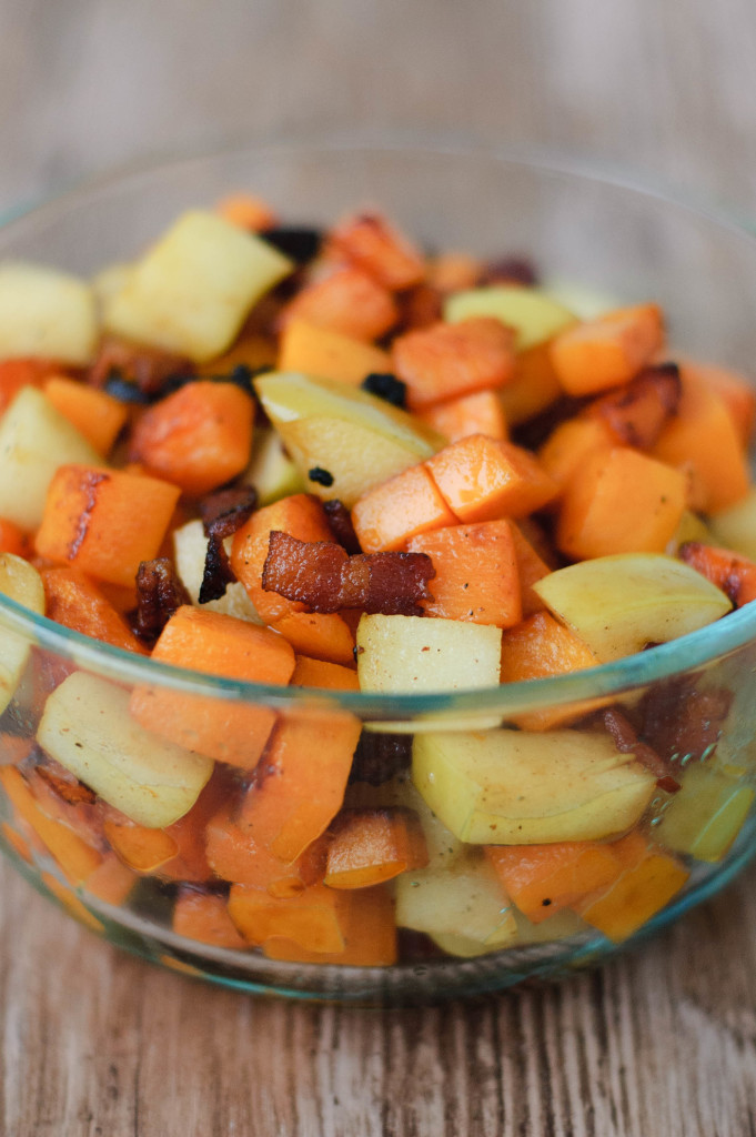 A bowl of harvest toppings, including bacon, green apple, and pumpkin.