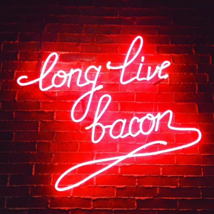 "red neon sign saying ""long live bacon"" in cursive."
