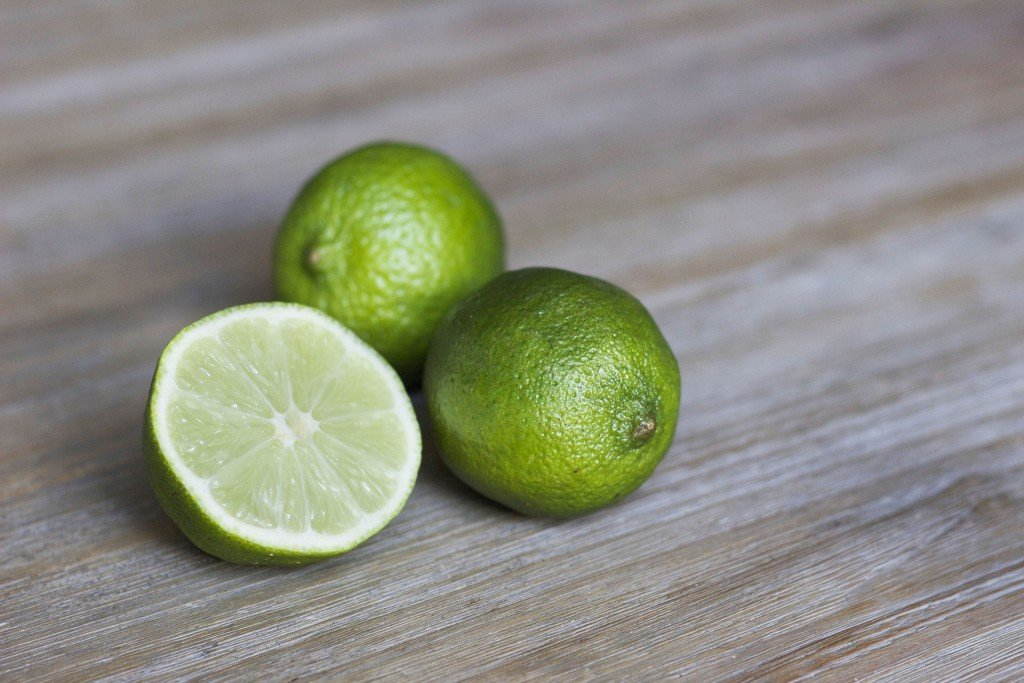 Close up of whole and cut limes on a wooden board.