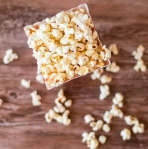 Overhead photo showing homemade buttered popcorn inside a container. Popcorn spills on the table.