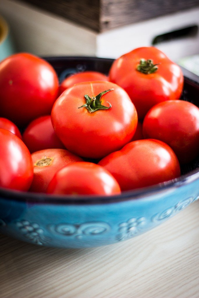 A blue bowl filled with a lot of tomatoes.