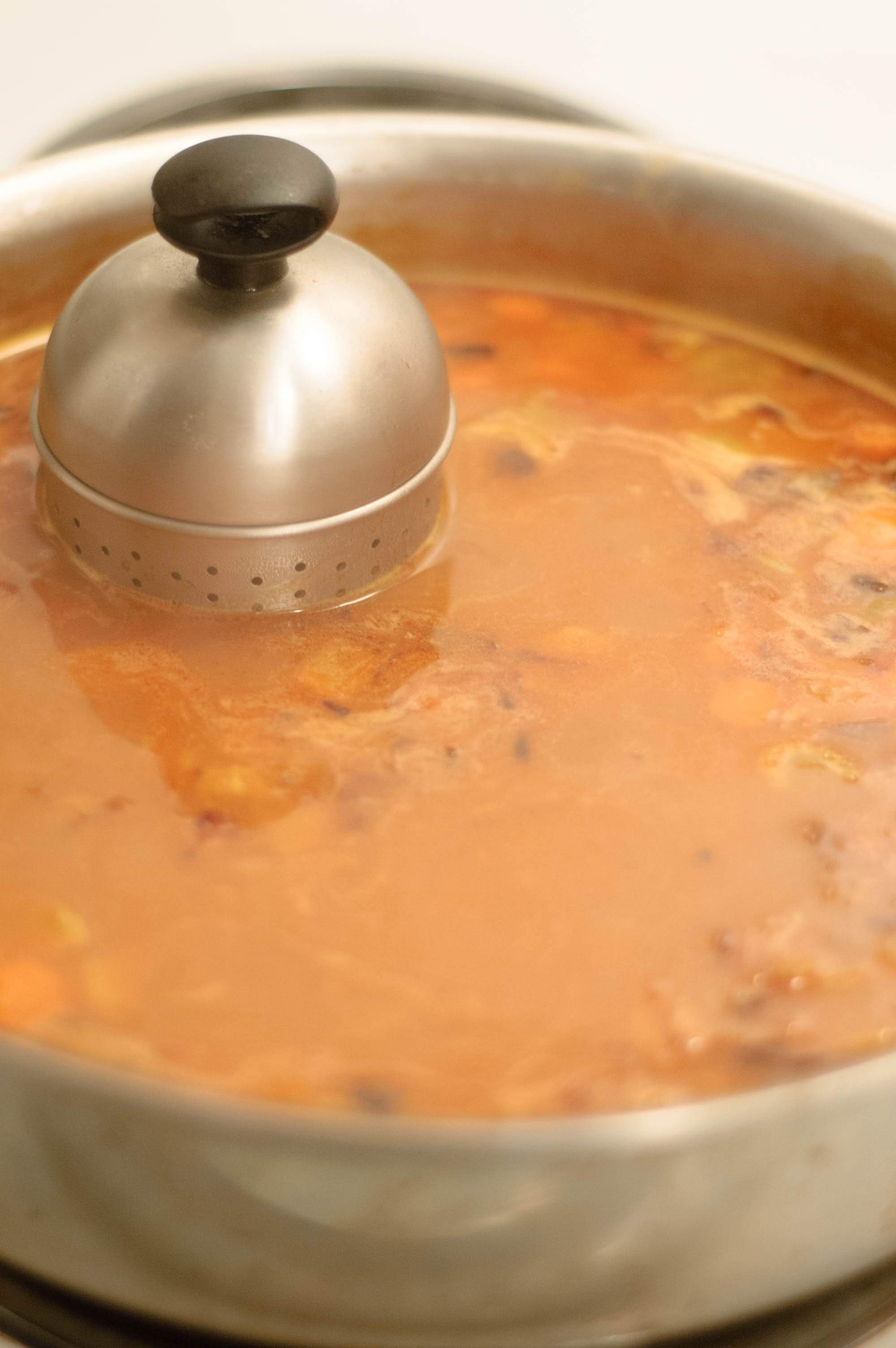 A spice strainer in a simmering sauce pan of espagnole sauce