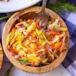 A wooden bowl of rainbow carrot salad with a fork in it.