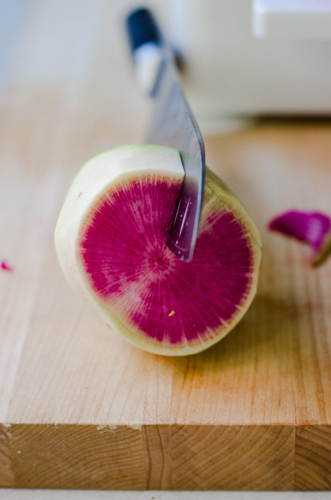 A knife cutting into a watermelon radish.