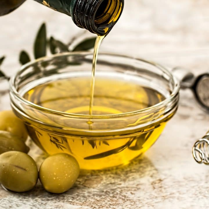 a bottle pouring olive oil into a bowl surrounded by olives.