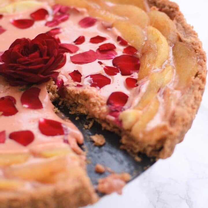 rose curd and white peach tart with a piece missing. It has an edible rose in the middle.