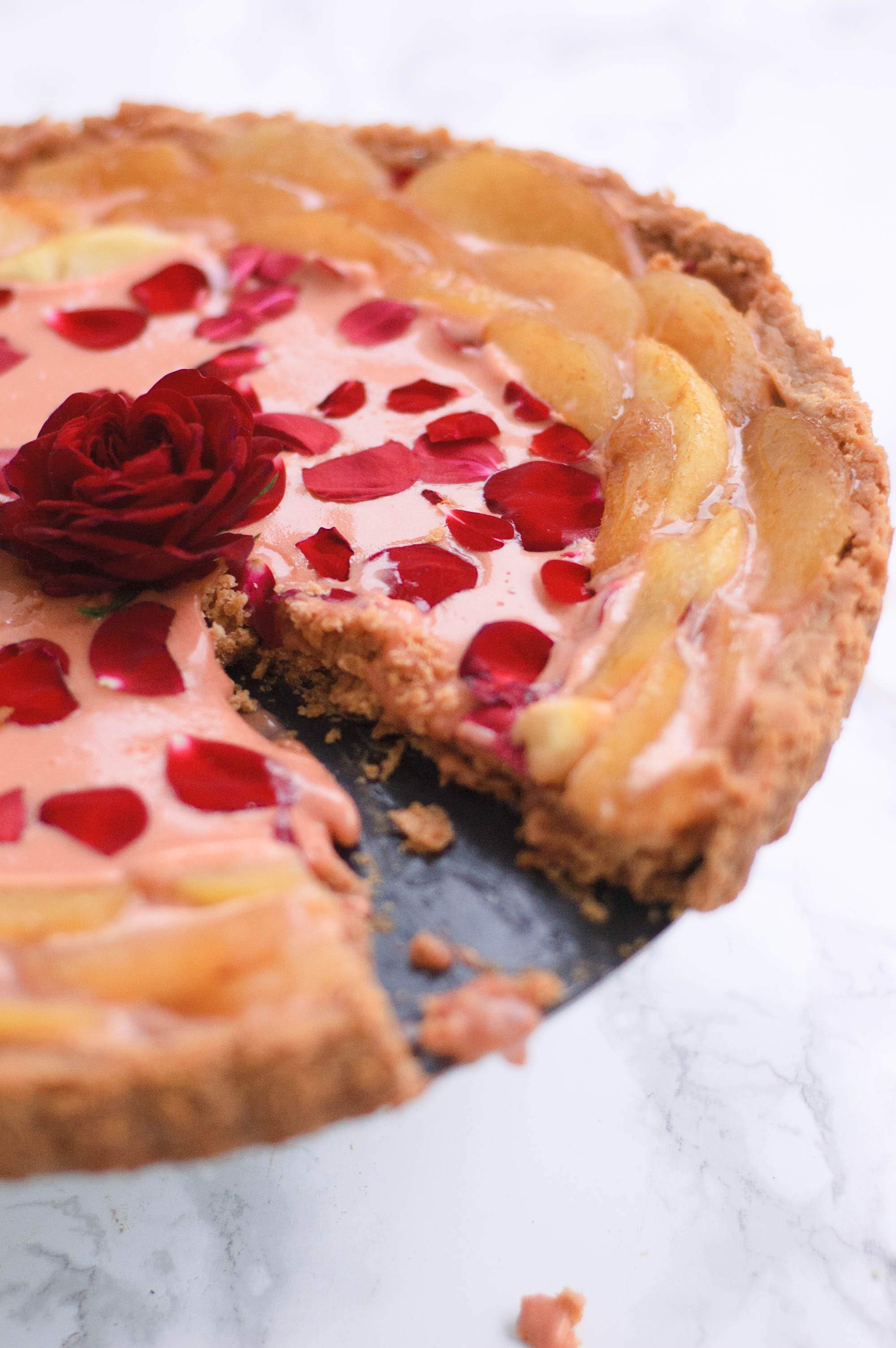 the rose curd and white peach tart with a piece missing from it.  It has an edible rose in the middle.