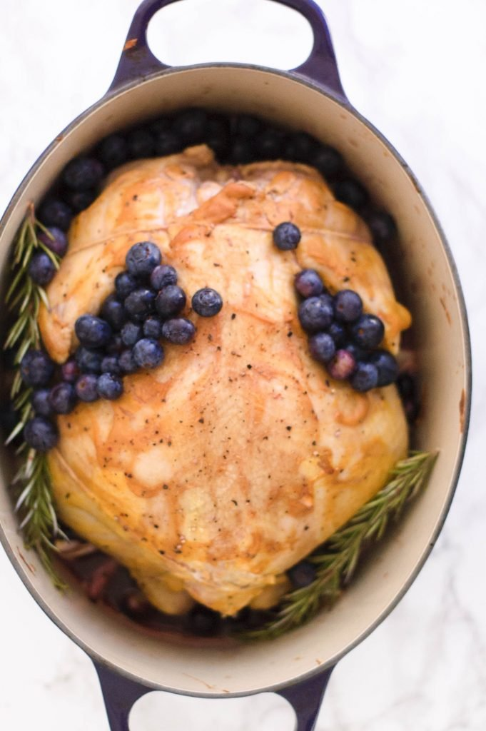 A whole roasted chicken topped with blueberries in a dutch oven.