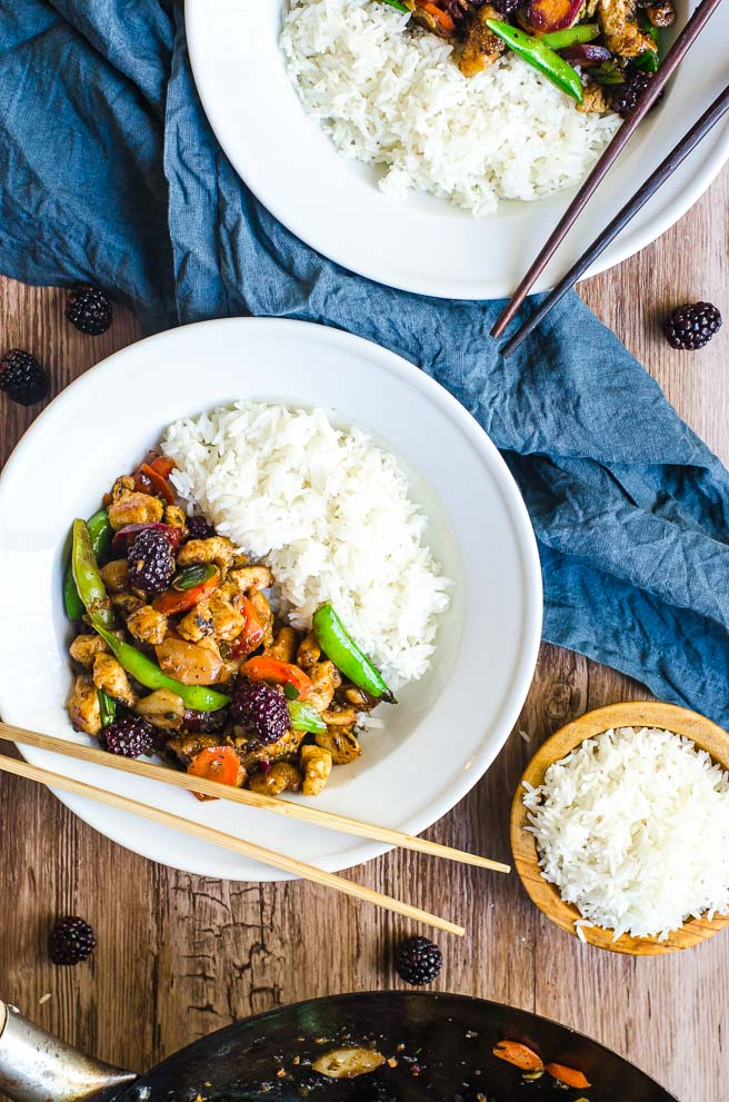 Two bowls of stir fry next to a wok and bowl of white rice.