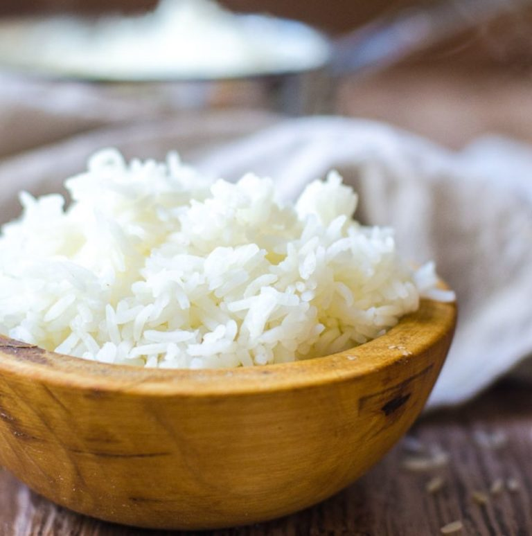 Closeup of a wooden bowl filled with white rice in front of a pot of cooked rice.