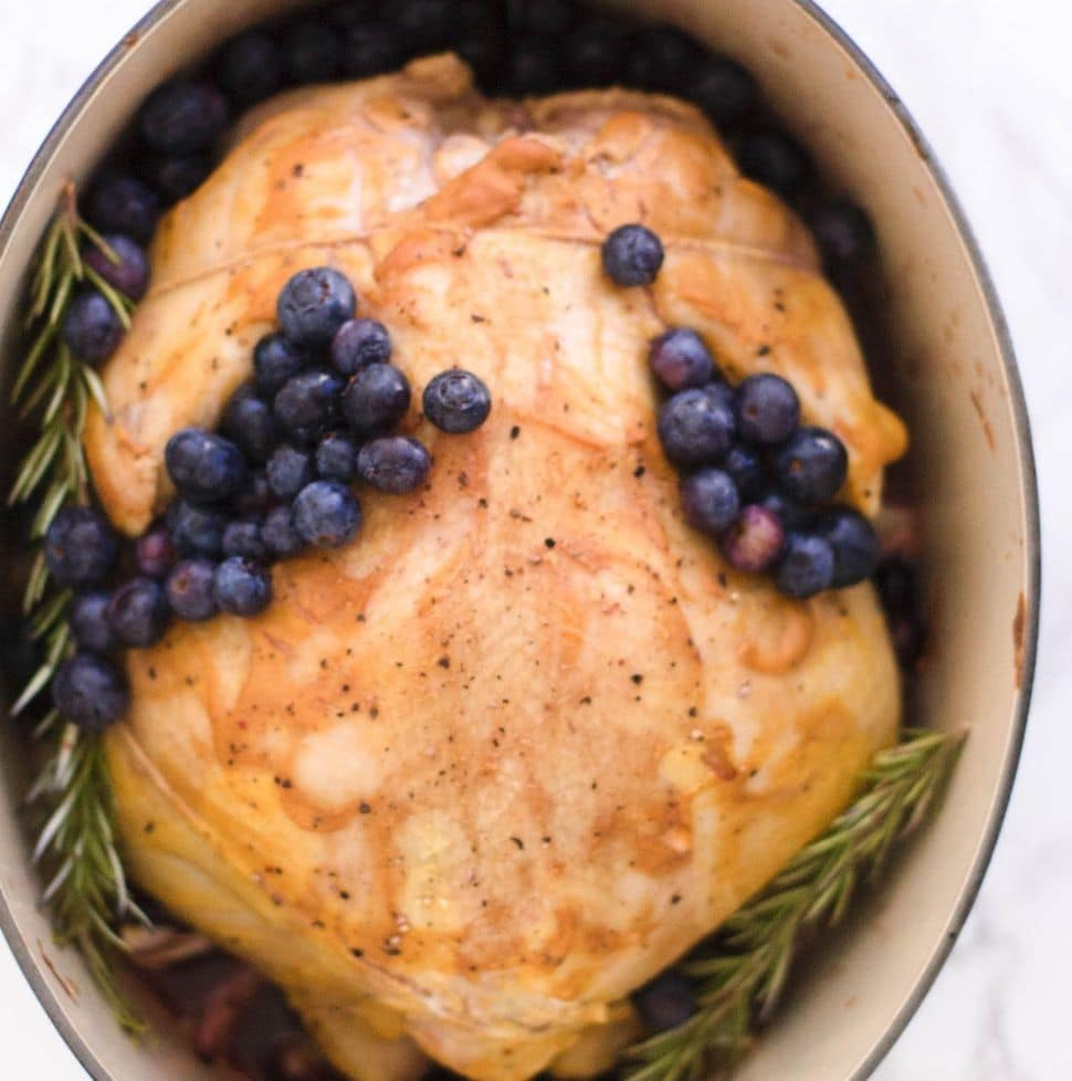 A whole roasted chicken garnished with blueberries and rosemary in a dutch oven.