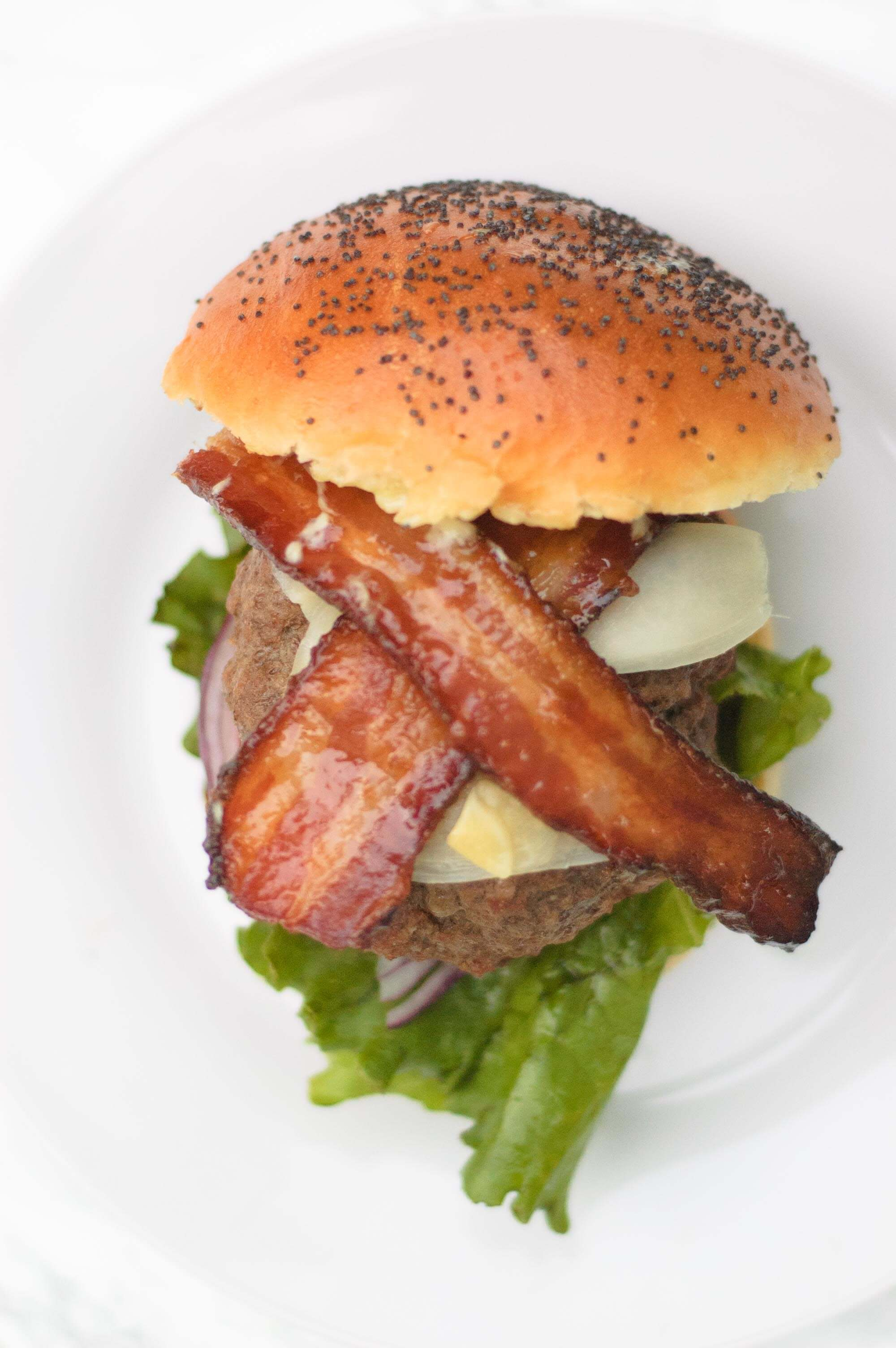 overhead view of the wasabi burger. The bacon is crisscrossed and the bun is on the side.