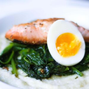 seared salmon and a medium boiled egg on wilted spinach and grits in a white bowl