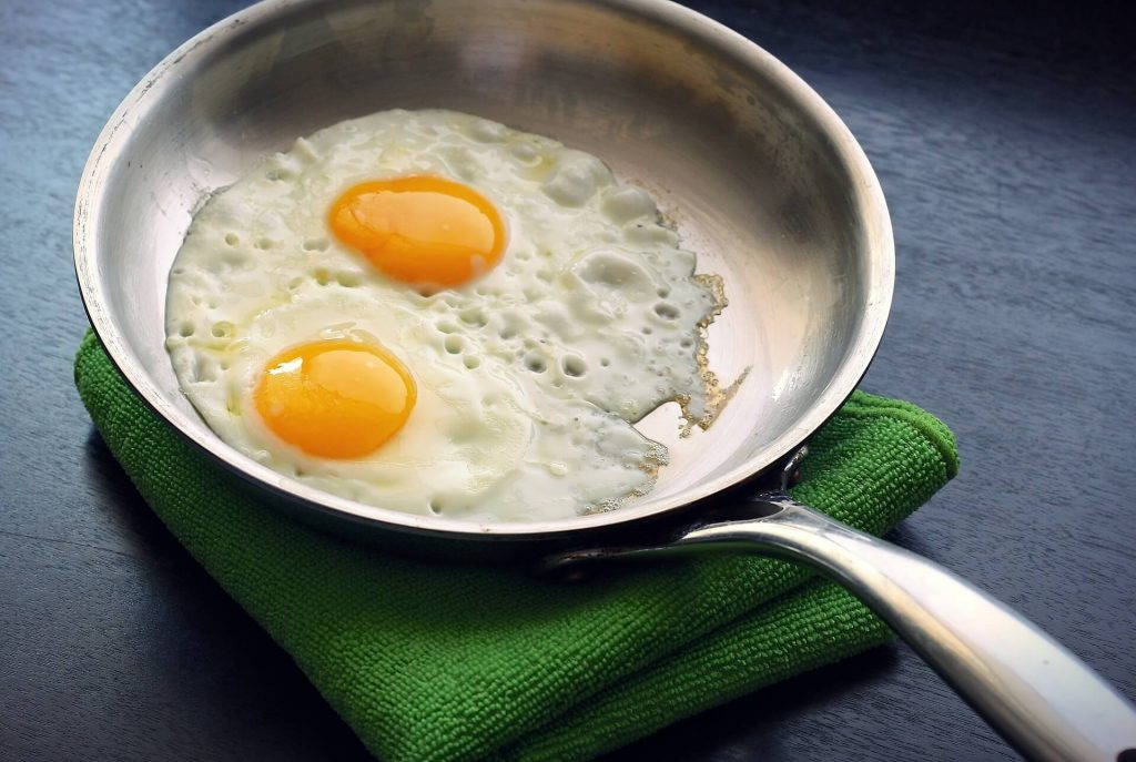 A stainless steel pan making fried eggs on a green towel