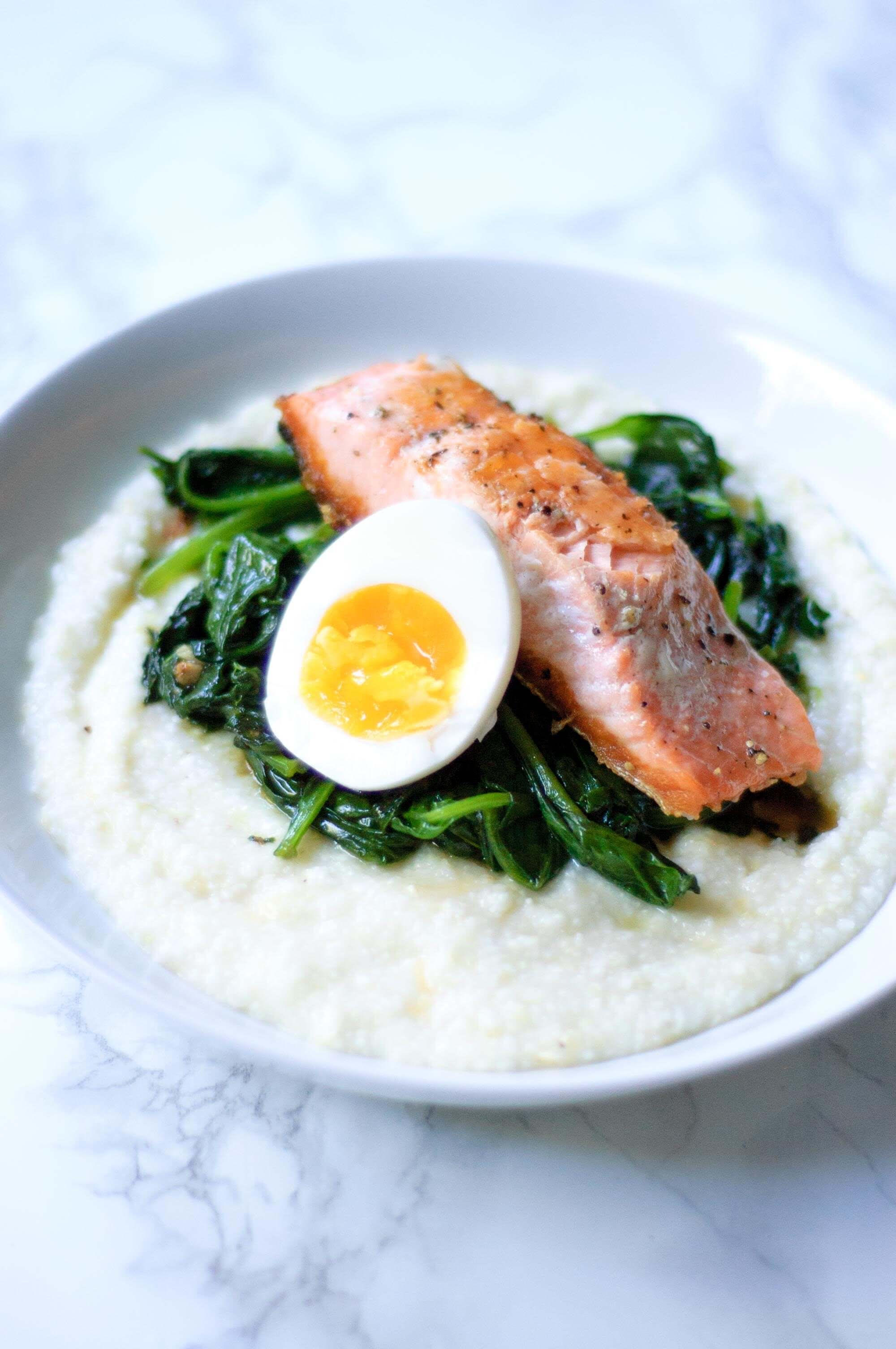 half of a boiled egg next to a serving of salmon with spinach and grits in a white bowl.