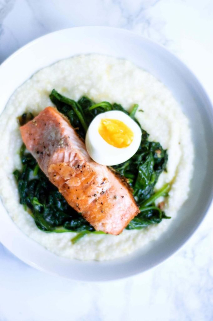 overhead image of salmon and grits in a white bowl