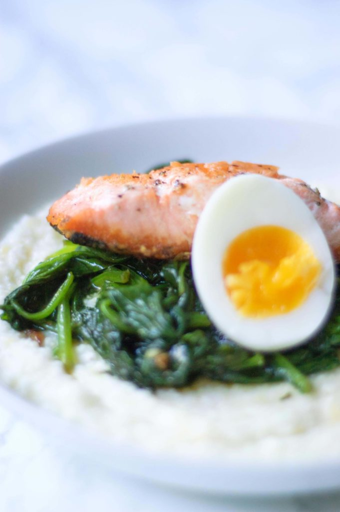 closeup image of half of a medium boiled egg next to wilted spinach and a salmon filet