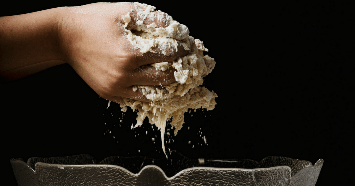 Hands lifting dough out of a clear bowl.