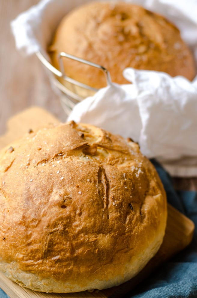 Two loaves of olive oil bread. One in a basket