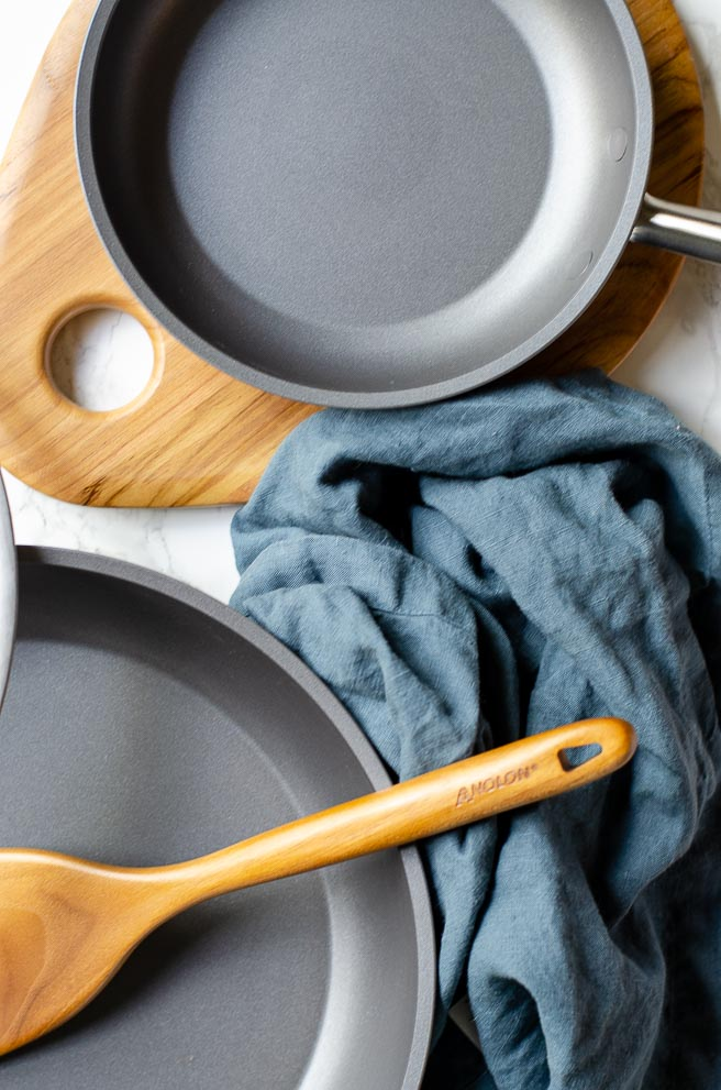 overhead shot of two nonstick frying pans with wooden utensils and a blue napkin