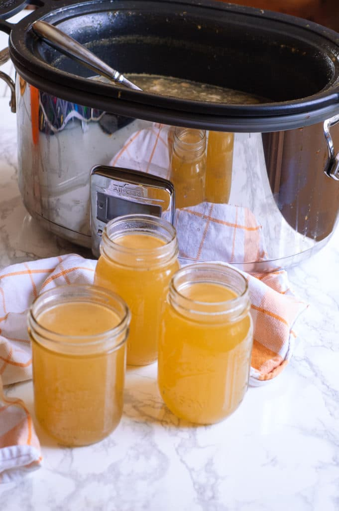 Homemade turkey stock in front of an all-clad slow cooker
