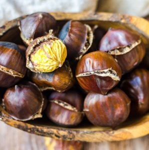 A wooden bowl filled with freshly roasted chestnuts. One is peeled.