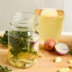 a mason jar of white wine and fresh herbs marinade next to ingredients