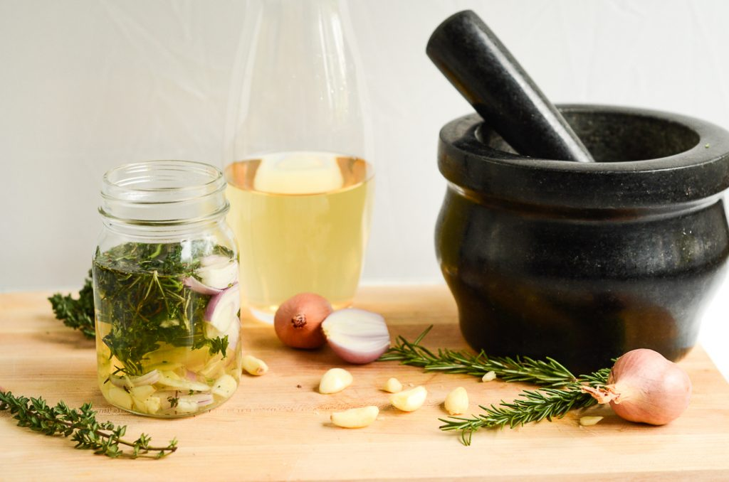 a mortar and pestle and ingredients on a cutting board.