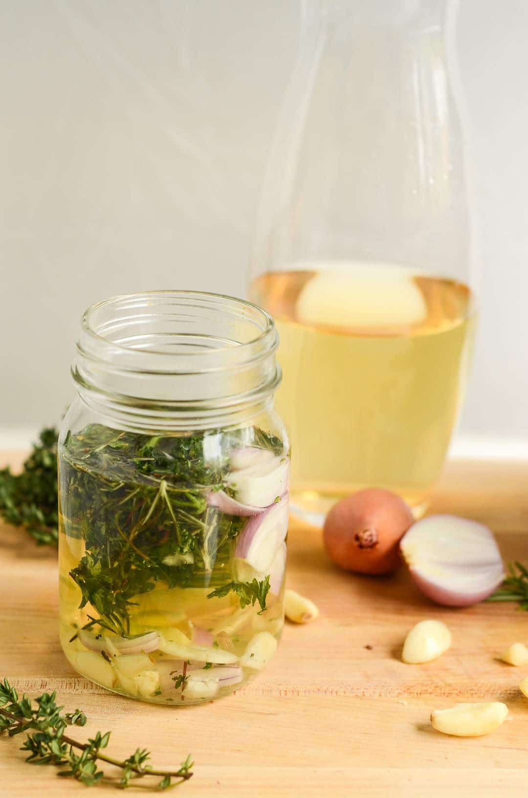 carafe of white wine behind mason jar of White Wine and Fresh Herbs Marinade
