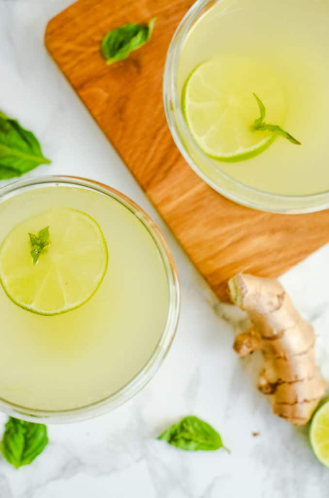 Overhead image of Two cocktail glasses of basil ginger gimlet with ginger, limes, basil and a cocktail shaker