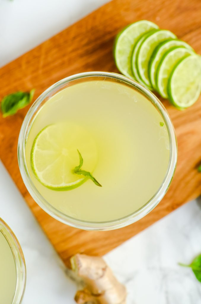 Overhead image of one basil ginger gimlet in a cocktail glass with limes and fresh basil