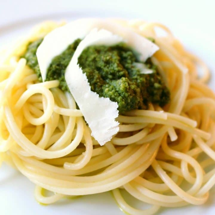 A pile of pesto and shaved parmesan on top of a plate of cooked spaghetti.