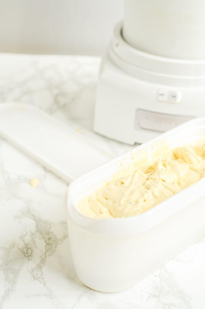 Tub of custard ice cream next to cuisinart ice cream maker