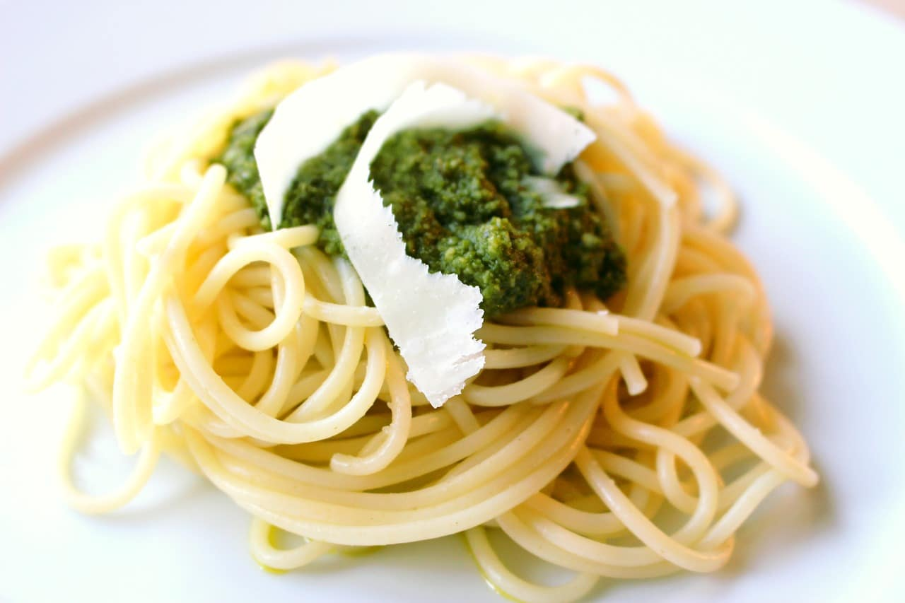 cooked spaghetti topped with pesto and a ribbon of parmesan cheese