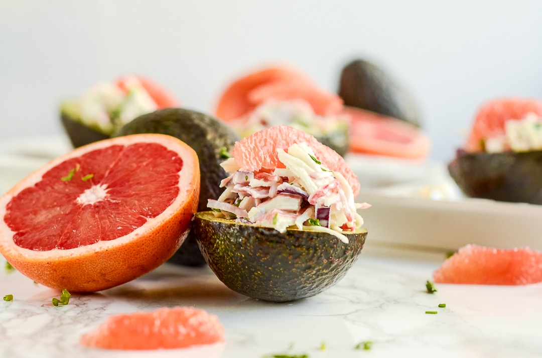 half an artichoke stuffed with crab and grapefruit next to half a grapefruit