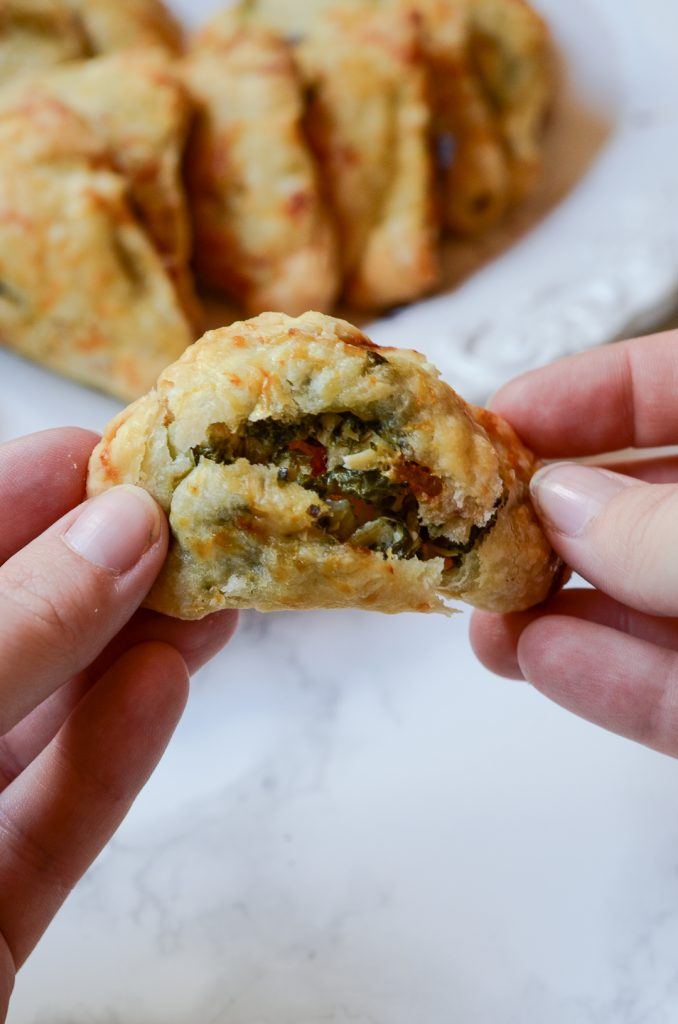 Hands breaking apart a mini hand pie to show bacon, spinach, artichoke, chicken filling