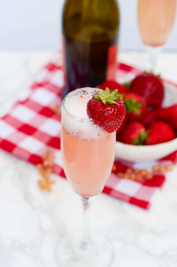 Overhead image of a glass of Bellini with bowl of strawberries and Prosecco bottle