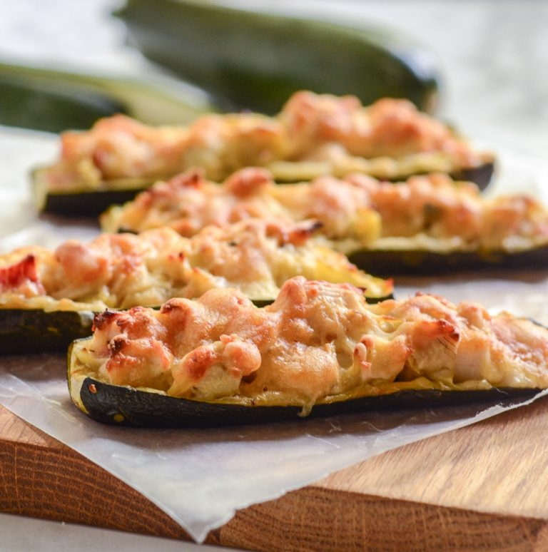 side view of four crab and artichoke stuffed zucchini on wax paper