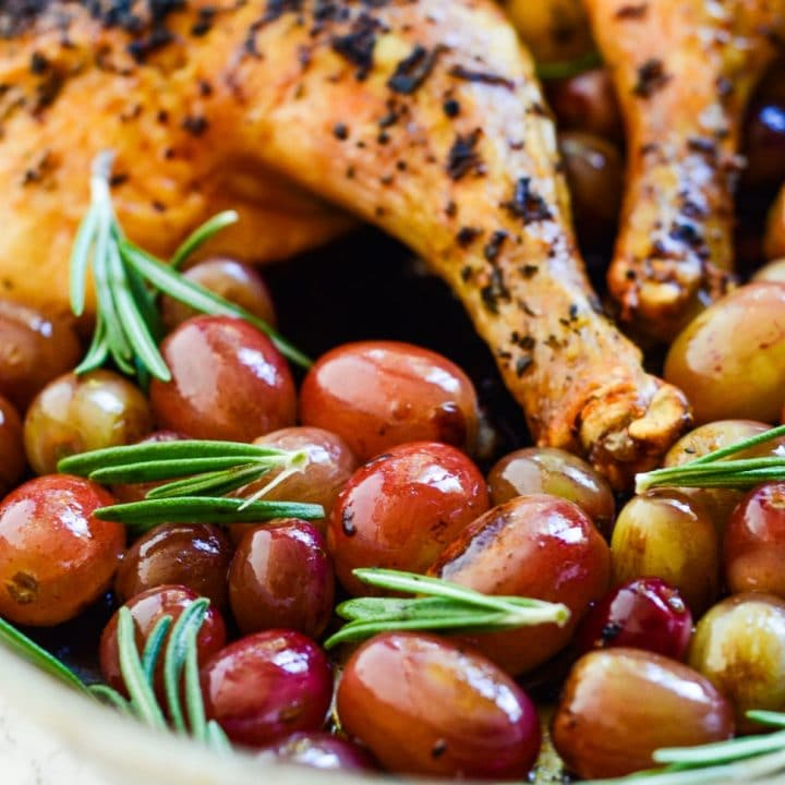 a pan with roasted grapes and a spatchcock chicken
